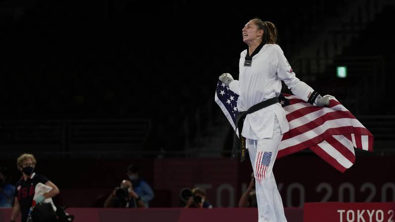 Anastasija Zolotic of the United States celebrates as she holds the American flag after winning...
