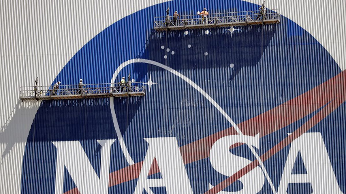 Workers near the top of the 526 ft. Vehicle Assembly Building at the Kennedy Space Center spruce up the NASA logo standing on scaffolds in Cape Canaveral, Fla., Wednesday, May 20, 2020. A SpaceX Falcon 9 rocket scheduled for May 27 will launch a Crew Dragon spacecraft on its first test flight with astronauts on-board to the International Space Station. (Source: AP Photo/John Raoux)