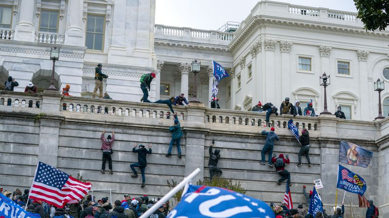 Supporters of President Donald Trump climb the west wall of the U.S. Capitol on Wednesday, Jan....