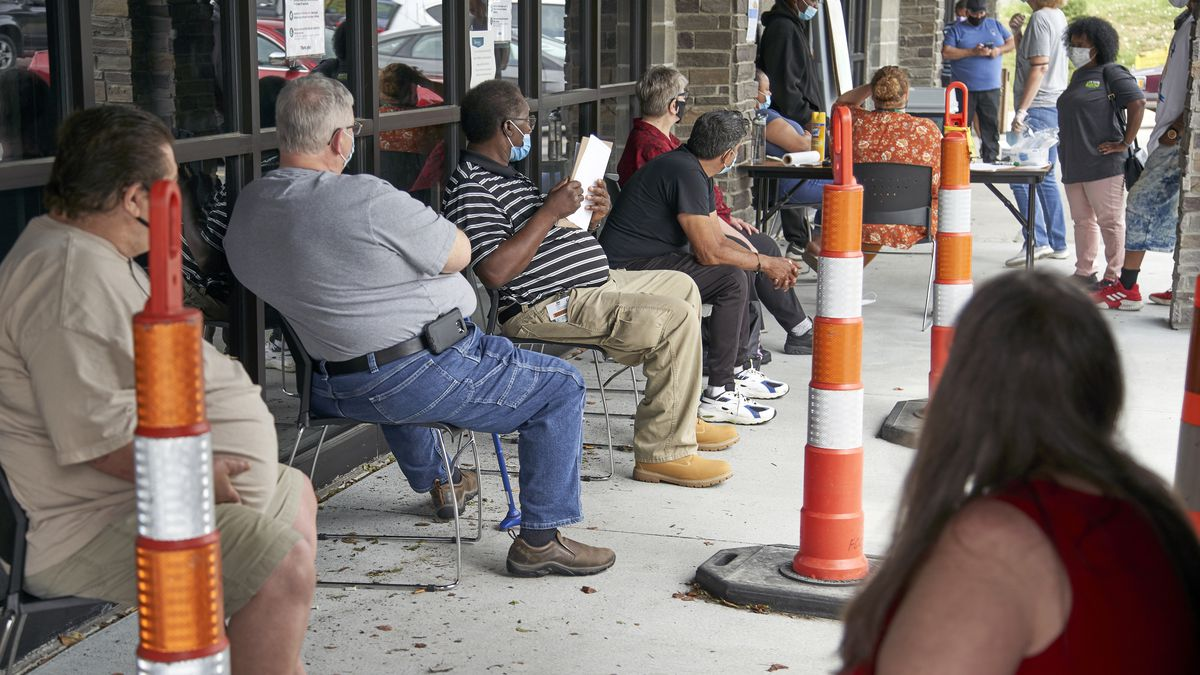 FILE - In this July 15, 2020, file photo, job seekers exercise social distancing as they wait...