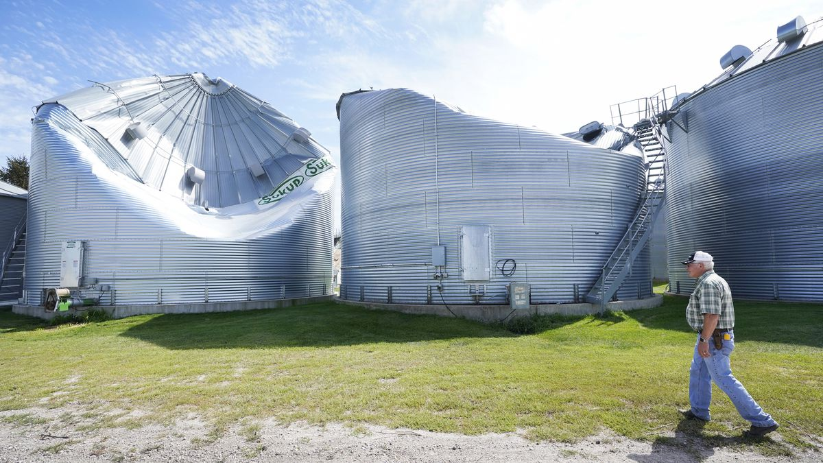FILE - Rod Pierce looks at grain drying bins on his farm that were damaged in the derecho earlier this month, Thursday, Aug. 20, 2020, near Woodward, Iowa. Pierce is among hundreds of Iowa farmers who are still puzzling over what to do next following the Aug. 10 derecho, a storm that hit several Midwestern states but was especially devastating in Iowa as it cut west to east through the state's midsection with winds of up to 140 mph.